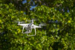 Drone in flight, green trees in the background, selective focus on the drone.  royalty free stock images