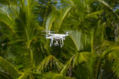 Drone in flight, green trees in the background, selective focus on the drone.  stock photo
