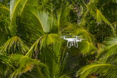 Drone in flight, green trees in the background, selective focus on the drone royalty free stock images