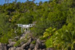 Drone in flight, green trees in the background, selective focus on the drone.  royalty free stock photo