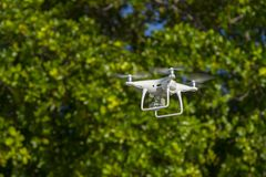 Drone in flight, green trees in the background, selective focus on the drone.  stock images