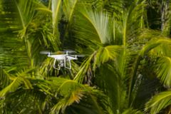 Drone in flight, green trees in the background, selective focus on the drone stock image
