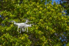 Drone in flight, green trees in the background, selective focus on the drone.  royalty free stock image