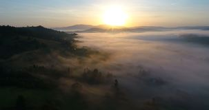 Drone flight over dreamy foggy mountain village during sunrise