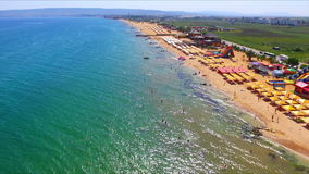Drone flight over the sand beach of Crimea with umbrellas stock footage