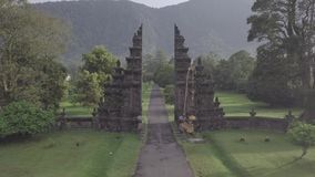 Drone flight over stunning view of stone gates and mountain on Bali, Indonesia. Near golf club stock video