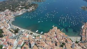 Top view of Spanish town Cadaques and blue bay. Drone flight over tiled roofs, narrow streets, white houses, church of resort coastal town, boats and yachts on a stock footage