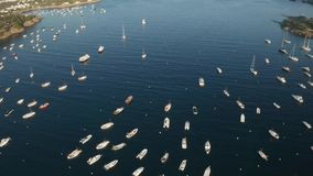 Drone flight over yachts in blue bay near Cadaques. Aerial view of anchored white yachts in beautiful large bay among capes. Drone shot of resort town Cadaques stock video