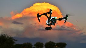 DRONE In Flight - Professional Camera (UAV / UAS) at Sunset. Camera drone hovering in front of a cloud at sunset royalty free illustration