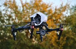 DRONE In Flight - Professional High Tech Camera UAV / UAS. Camera drone hovering in front of trees and foliage Stock Photography
