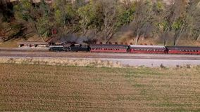 Drone Flight of a Steam Engine and Train Pulling out of a Station in Pennsylvania USA. Drone Flight of a Steam Engine and Train Blowing Smoke in Pennsylvania stock footage