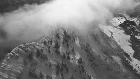 A drone flight in the Swiss mountains through the fog stock video footage