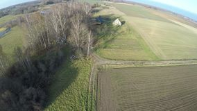 Drone fly up over farmland fields in autumn. Drone fly up over farmland fields and old wooden house in autumn stock video footage