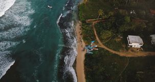Drone flying above beautiful foaming sea waves reaching ocean coast line with tropical trees, houses, hotels and boats. Drone flying above beautiful foaming sea stock video