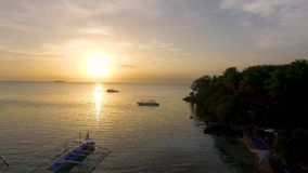 Aerial: Beautiful Beach Sunset With Wooden Boat In Moalboal, Cebu. Drone Flying Above Beautiful Sea At Sunset With Wooden Boats In The Distance At Summer stock footage