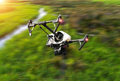 Drone flying above green field. In blur motion Stock Photos