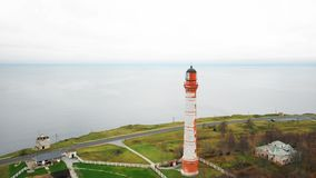 Drone flying above scenic old lighthouse and picturesque farm buildings on overcast Baltic sea shore on cloudy day. Amazing atmospheric aerial shot of idyllic stock footage