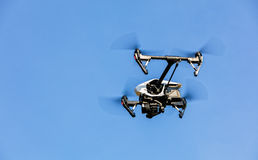 Drone flying against blue sky background Royalty Free Stock Photo