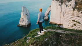 Drone flying around happy young travel blogger man watching breathtaking sunset view on top of coast cliff rock Etretat. stock video footage