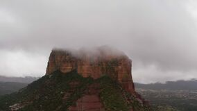 Drone flying around massive red rock in Sedona during cloudy day