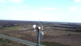 Drone flying around outdoor repeater base station tower, technician works on top of cellular antenna stock footage