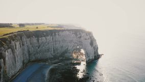 Drone is flying away from young happy tourist newlywed couple in epic natural rocky arch at famous white Normandy cliffs stock video footage