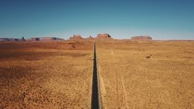 Drone flying backwards high above empty sandstone desert road in Monuments Valley, Arizona with flat mountains skyline.