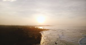 Drone flying backwards over epic sunset reflection in white ocean waves reaching amazing tropical paradise coast line. stock video footage