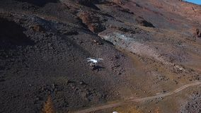 Drone flying in the canyon, in a aerial shot. a white large quadrocopter or drone flies among the peaks in the mountains stock video footage