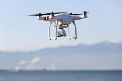 Drone flying with clear blue sky. KAGAWA, JAPAN - DECEMBER 15, 2016: White remote controlled Drone Dji Phantom 3 equipped with high resolution video camera Stock Photos