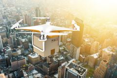 Drone flying with a delivery box package over a sunset city Royalty Free Stock Photography