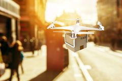 Drone flying with a delivery box package in the sunset Stock Photography
