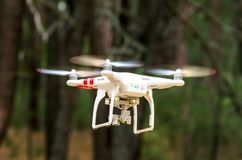 Drone flying in the forest. Drone or quadricopter flying in the forest surrounded by trees stock photos