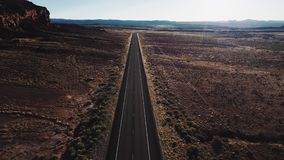 Drone flying forward over straight desert highway road in USA wilderness near massive rocky mountain and beautiful sky.
