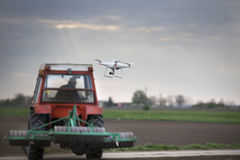 Drone flying in front of tractor. Drone flying over field with tractor in background. Innovation in agricultural production royalty free stock photos