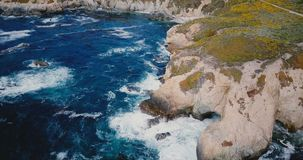 Drone flying high above beautiful ocean shore, foaming waves crash over large rocks at summer Big Sur scenery California