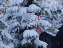 Drone flying in winter. A drone flying high above a forest covered with fresh snow in a bright sunny winter day stock photo