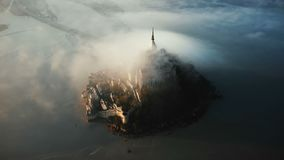 Drone flying high around amazing Mont Saint Michel island castle fortress covered with massive sunrise fog clouds flow. Drone flying high around amazing Mont stock footage