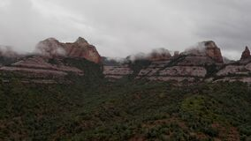 Drone flying by massive red rocks in Sedona during cloudy day