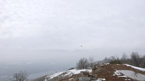 Drone flying in the mountains, cloud weather, snow. People playing with drone quadcopter for filming purpose. stock footage