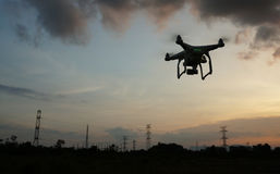 Drone flying near electricity power lines tower. At sunset royalty free stock photography