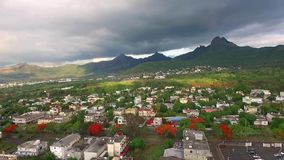 Drone flying over the Belle Etoile town in Mauritius, close to Port Louis. Stormy Sky and mountain in Background stock footage