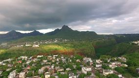 Drone flying over the Belle Etoile town in Mauritius, close to Port Louis. Stormy Sky and mountain in Background stock video footage