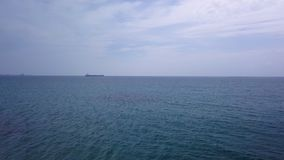 Drone is flying over blue sea water in daytime. Ship in horizon stock video footage