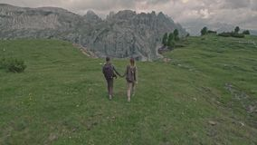Drone flying over a couple who walks on the field in Tre Cime di Lavaredo stock video