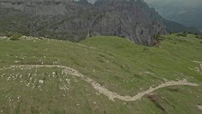 Drone flying over a couple who walks on the field in Tre Cime di Lavaredo stock footage