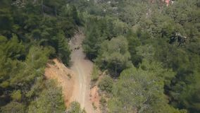 Drone is flying over dirt road in mountains in spring day stock video footage