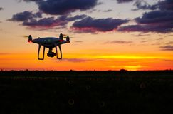 Drone is flying over the field at sunrise. Modern technological background - silhouette of flying machine in glowing red sunset sky Stock Images