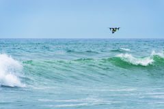 Drone flying over the the ocean. Drone flying over the waves on the ocean stock image
