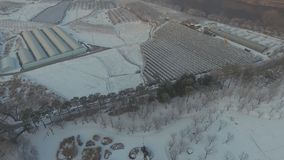 Drone flying over a snow covered field in a public park. Drone flying over a snow covered public park surrounded by trees next to a small farm on a hazy morning stock video
